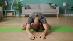Young man are doing yoga at living room in the morning stock video footage