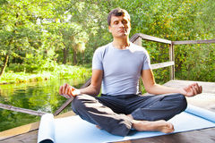 Young man doing yoga (lotus pose) in the park Stock Photos