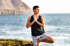Young man doing yoga and meditating in tree position at sea beach royalty free stock image
