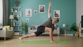 Dolly out of adult man doing yoga in the morning in his living room stock video