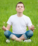 A young man doing yoga at park Stock Image