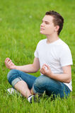 A young man doing yoga at park Stock Photos