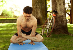 Young man doing yoga posture in the grass Royalty Free Stock Photo