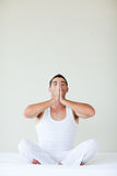 Young man doing yoga sitting in bed Royalty Free Stock Photography