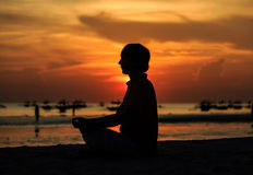 Young man doing yoga on sunset beach Royalty Free Stock Photography