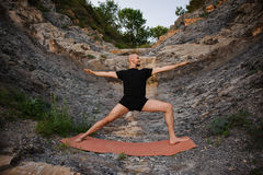 Young man doing yoga in warrior pose on rocks royalty free stock photography