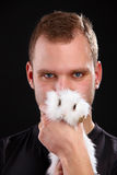 Young man and domestic rabbit on black background Royalty Free Stock Image