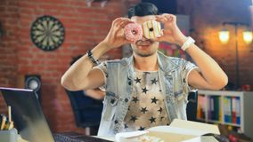 Young man with donats in his office stock images