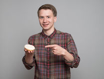 Young man with donut. Young man holding glaced donut  on grey background Stock Photos