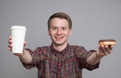 Young man with donut. Young man holding glaced donut and paper cup  on grey background Stock Image