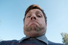 Young man with a double chin - the result of poor lifestyle. View up on blue sky royalty free stock photos