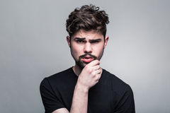 Young man in doubting Royalty Free Stock Images