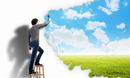 Young man drawing a cloudy blue sky. On the wall Royalty Free Stock Photo