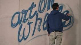 Young man drawing graffiti on a wall with a spray can stock footage