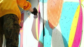 Young man drawing graffiti on wall with spray can Royalty Free Stock Images