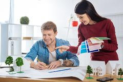 Young man drawing while his colleague holding color palettes. Pleasant discussion. Cheerful enthusiastic young engineer smiling and drawing while his pretty royalty free stock image