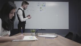 Young man drawing pie chart on the office board showing information to female colleague involved in work. Brunette woman. Young man drawing pie chart on the stock video footage