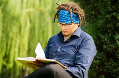 Young man with dreadlocks is reading a bookin the park Stock Images