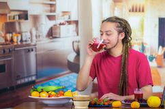 Young man with dreads enjoying healthy breakfast, eating fruits, drinking smoothie and smiling, home kitchen background.  Royalty Free Stock Photo