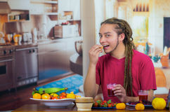 Young man with dreads enjoying healthy breakfast, eating fruits, drinking smoothie and smiling, home kitchen background.  Royalty Free Stock Photography