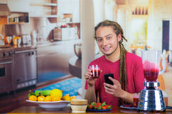 Young man with dreads enjoying healthy breakfast, eating fruits, drinking smoothie and smiling using mobile phone, home. Kitchen background Royalty Free Stock Images