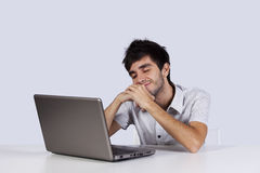 Young man dreaming in front of his laptop. Young man with happy dreams in front of his laptop Stock Photo