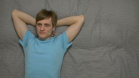 Young Man Dreams On Bed. Resting daytime sleep thinks positive smile male 30 years old in blue t shirt caucasian white european lying on the bed gray sheet top stock footage
