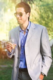 Young man with dress, sunglasses and cocktail in hand. Outdoors aperitivo party Royalty Free Stock Images