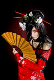 A young man dressed as a geisha. Over dark background royalty free stock image