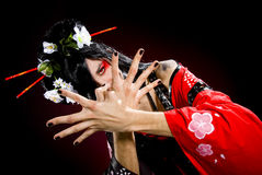 A young man dressed as a geisha. Over dark background stock photo