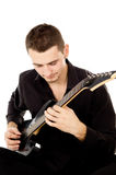 Young man dressed in black clothes sits and plays the guitar Stock Image