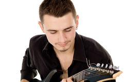 Young man dressed in black clothes sits and plays the guitar Royalty Free Stock Photography