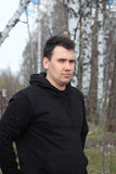 Young man dressed in black stands in spring forest Royalty Free Stock Image