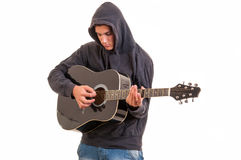Young man dressed in hoodie tring to understand how to play acous Stock Image