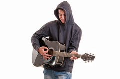 Young man dressed in hoodie try to understand how to play acous Stock Photos