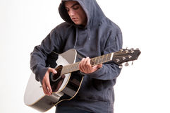 Young man dressed in hoodie try to understand how to play acous Royalty Free Stock Image
