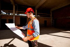 Young man dressed in shirt, orange work vest and helmet explore construction documentation on the building site inside stock photo