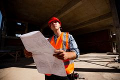 Young man dressed in shirt, orange work vest and helmet explore construction documentation on the building site inside royalty free stock photography