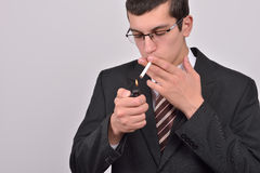 Young man dressed in tuxedo lighting cigarette Stock Photos