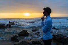 Man Looking Ocean Horizon Rocks Silhouetted. Young man dressed white shirt black longs bare feet looking out to horizon silhouetted on beach ocean rocks at dawn Royalty Free Stock Images