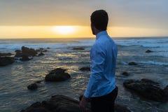 Man Looking Ocean Horizon Rocks Silhouetted. Young man dressed white shirt black longs looking out to horizon silhouetted on beach ocean rocks at dawn sunrise Royalty Free Stock Photos