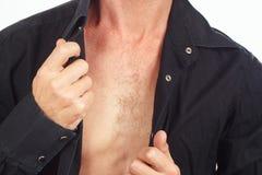 Young man dresses his black shirt closeup Royalty Free Stock Image