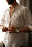Young man dresses shirt and fastens buttons. stock photography