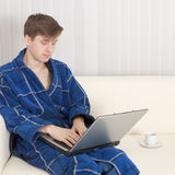 Young man in dressing gown with laptop Stock Photos