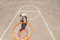 Young Man Dribbling Basketball Below Net on Court Royalty Free Stock Photo