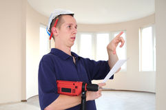 Young man with drill and paper hat Stock Photos
