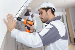 Young man drilling wall with drill perforator Stock Images