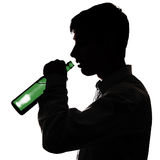 Young Man drink a Beer. Silhouette of Young Man drinks a Beer on the White Background Royalty Free Stock Photo