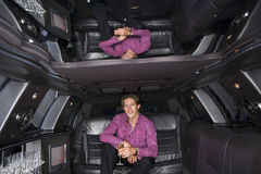 Young man with drink in limousine, reflection in ceiling, smiling, portrait Royalty Free Stock Photos