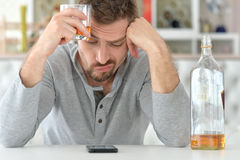 Young man drinking alcohol. In bad mood Stock Photo